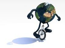 与胳膊和腿的地球乘坐单轮脚踏车 库存照片