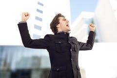 与胳膊的商人庆祝他的成功的 免版税库存照片