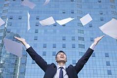 年轻与胳膊的商人投掷的纸在天空中 免版税图库摄影