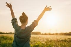 与胳膊的女性青少年的女孩立场感受自由被舒展对天空 库存图片