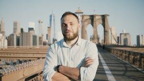 与胳膊的年轻正面男性白种人商人横渡了看照相机,微笑在布鲁克林大桥,纽约4K 影视素材