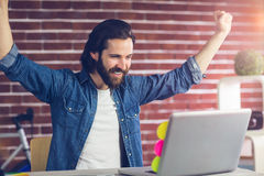 与胳膊的微笑的创造性的商人提高了看膝上型计算机 免版税图库摄影