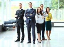 与胳膊的愉快的企业队在办公室横渡了 免版税库存照片