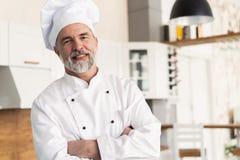 与胳膊的有吸引力的白种人厨师身分在餐馆厨房里横渡了 免版税库存图片