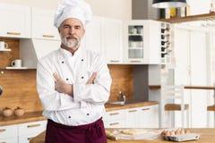 与胳膊的有吸引力的白种人厨师身分在餐馆厨房里横渡了 免版税库存照片