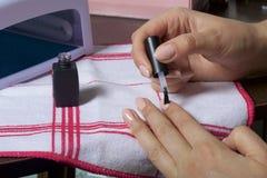 与胶凝体油漆的钉子涂层 妇女应用在她的钉子的指甲油 库存图片