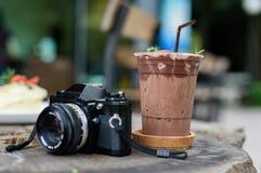 与胶卷相机的被冰的可可粉在木桌上 免版税库存照片