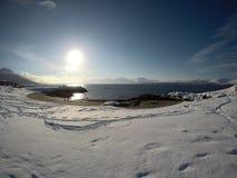 与脚印的长的多雪的领域与美丽的海湾、蓝色海湾和天空在一个晴朗的冬日 库存照片