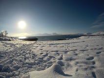 与脚印的长的多雪的领域与美丽的海湾、蓝色海湾和天空在一个晴朗的冬日 免版税库存照片