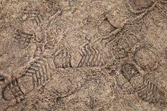 与脚印的冻结的路土 图库摄影