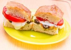 与腌汁muffaletta、蕃茄和m的素食热的三明治 图库摄影