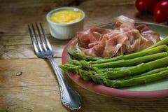 与腌火腿的绿色芦笋和蛋黄奶油酸辣酱在earthenw调味 库存照片