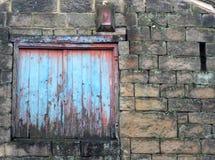 与腐朽的蓝色被绘的快门的上的窗口 免版税库存图片