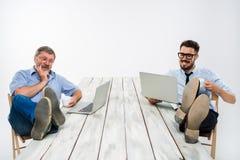 与腿的两个商人在研究膝上型计算机的桌 库存照片