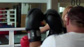 与腿的妇女训练kickboxing的命中有在拳击台的教练员的 影视素材