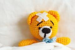 与膏药的不适的黄色玩具熊在头在白色卧室 免版税图库摄影