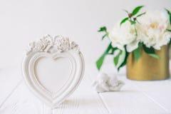 与膏药的心形的photoframe开花,两个古色古香的矮小的可爱的天使小雕象在白色木桌上的与花束 库存图片