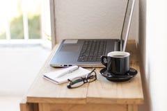 与膝上型计算机、咖啡、笔记本和玻璃的工作区 库存图片