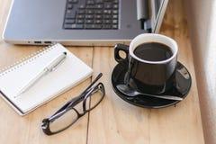 与膝上型计算机、咖啡、笔记本和玻璃的工作区 免版税库存图片