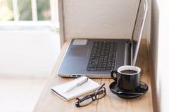 与膝上型计算机、咖啡、笔记本和玻璃的工作区 免版税库存照片
