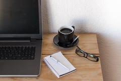 与膝上型计算机、咖啡、笔记本和玻璃的工作区 免版税图库摄影