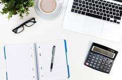 与膝上型计算机、咖啡杯和供应顶视图的办公桌桌 免版税库存照片