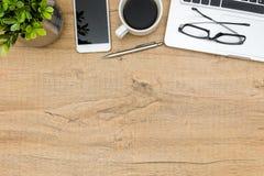 与膝上型计算机、智能手机、咖啡和供应的木办公桌桌 免版税库存照片