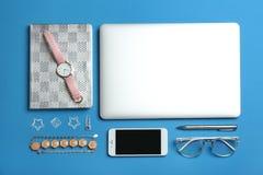 与膝上型计算机、智能手机和辅助部件的平的被放置的构成在颜色背景 图库摄影