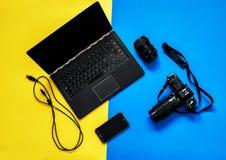 与膝上型计算机、照相机和机动性的黄色和蓝色背景 免版税库存照片