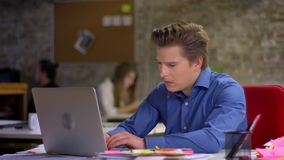 与膝上型计算机一起使用和咳嗽在办公室的中年白肤金发的商人画象  股票录像