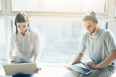 与膝上型计算机一起使用和坐在大明亮的窗口附近的男人和妇女 免版税库存照片