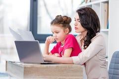 与膝上型计算机一起使用和看纸的女儿和母亲在办公室 库存图片