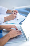 与膝上型计算机一起使用和采取笔记的医疗同事 免版税库存照片