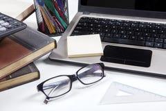 与膝上型计算机和书的玻璃在桌上 免版税库存照片