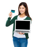 与膝上型计算机和信用卡的妇女展示 图库摄影