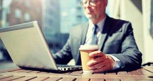 与膝上型计算机和咖啡户外的资深商人 库存照片