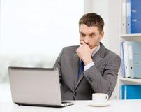 与膝上型计算机和咖啡的繁忙的商人 免版税库存照片