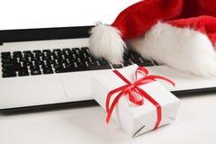 与膝上型计算机和圣诞节礼物和圣诞老人帽子的工作区在白色背景舱内甲板位置,顶视图,拷贝空间 免版税库存照片