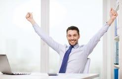 与膝上型计算机和文件的微笑的商人 免版税库存图片