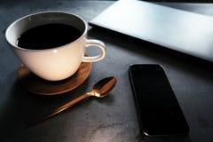 与膝上型计算机和智能手机的咖啡在具体桌上 免版税库存照片