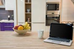 与膝上型计算机和果子的舒适现代厨房内部 库存图片