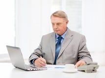与膝上型计算机和电话的繁忙的更老的商人 库存图片