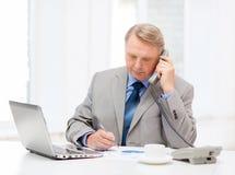 与膝上型计算机和电话的繁忙的更老的商人 免版税库存照片