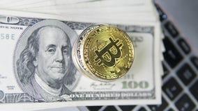 与膝上型计算机和的Bitcoin硬币美元 在一美元钞票和膝上型计算机的Bitcoin金黄硬币 Cryptocurrency 免版税库存照片
