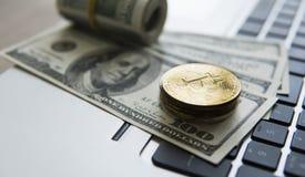与膝上型计算机和的Bitcoin硬币美元 在一美元钞票和膝上型计算机的Bitcoin金黄硬币 Cryptocurrency 免版税图库摄影