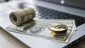与膝上型计算机和的Bitcoin硬币美元 在一美元钞票和膝上型计算机的Bitcoin金黄硬币 Cryptocurrency 库存图片