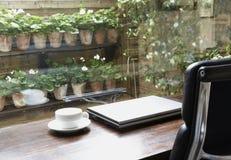 与膝上型计算机和空的咖啡杯的读书桌 库存照片