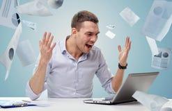 与膝上型计算机和纸呼喊的恼怒的商人 免版税库存图片