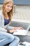 与膝上型计算机坐的台阶的十几岁的女孩研究 免版税库存图片