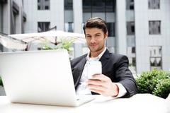 与膝上型计算机开会和使用手机的微笑的年轻商人 库存图片